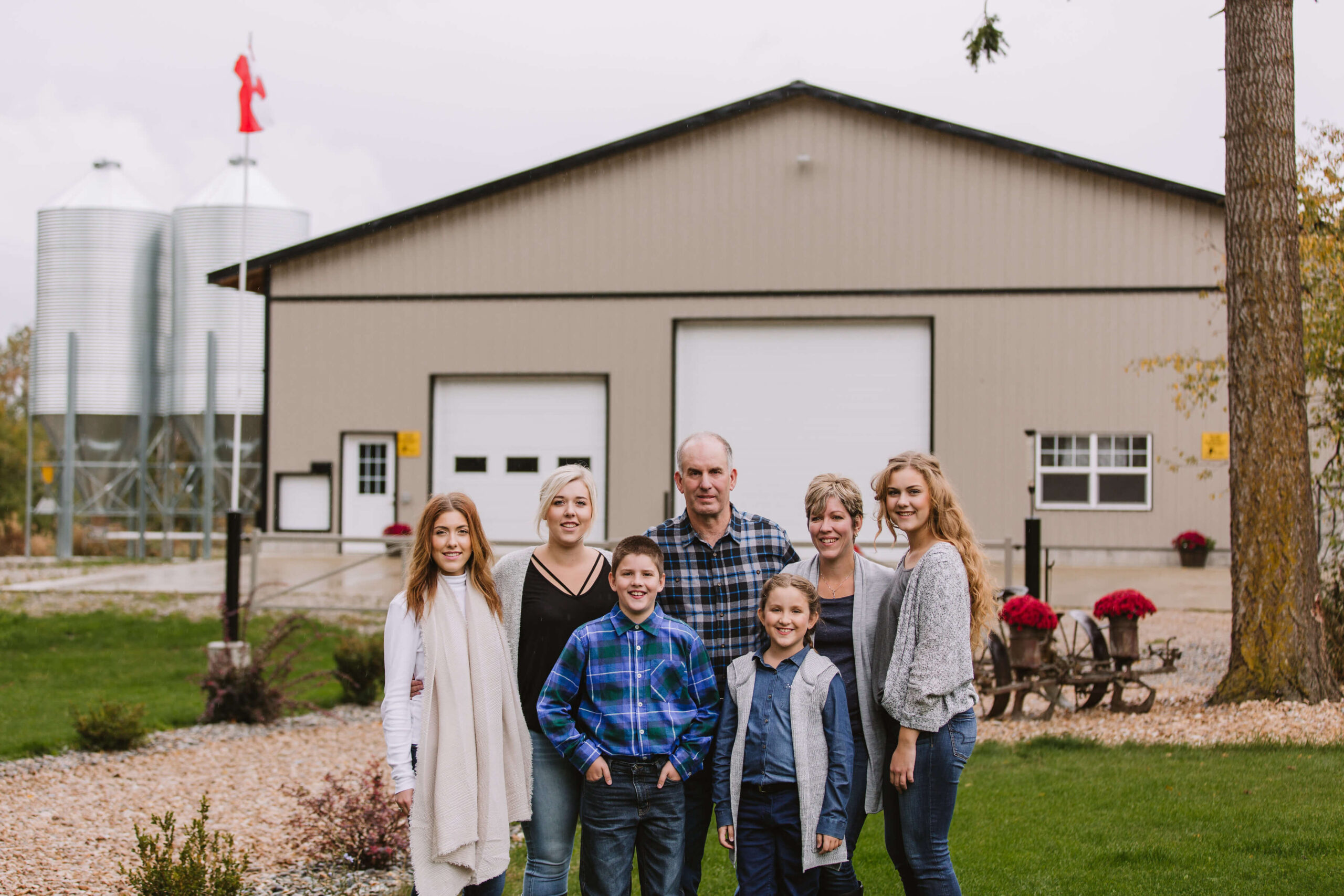 farmer family picture with farm in the back